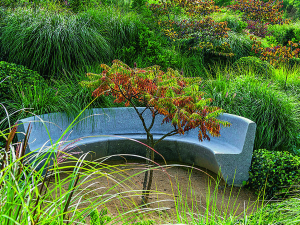 Длинной полукруглой скамье выделили почетное место в солнечном уголке сада. Ее размеры позволяют свободно разместиться здесь большой семье или компании друзей.