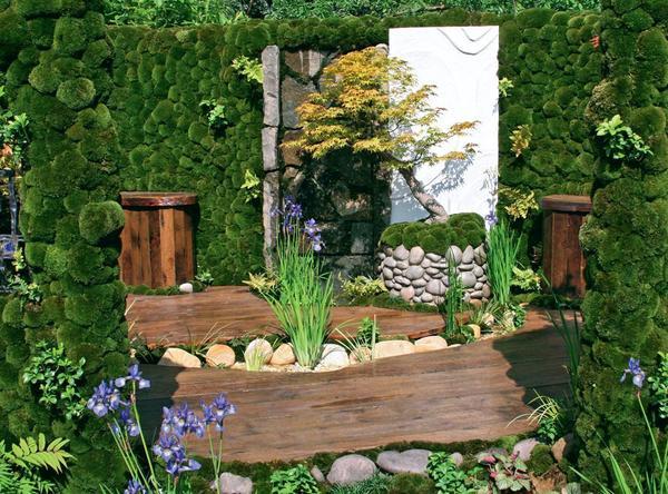 Бонсай, спрятанный в кадушку, декорированную галькой, - словно миниатюра в садовом интерьере.