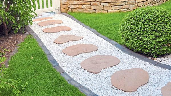 Гравийную дорожку всегда можно дополнить другим материалом, например каменными плитами.