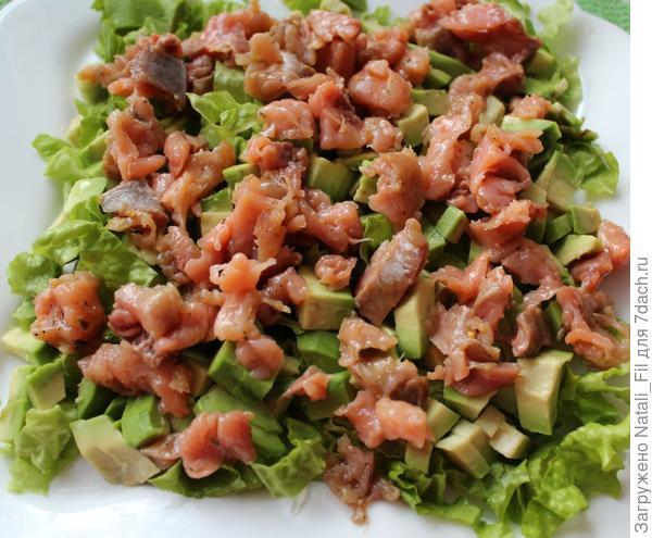 На авокадо выложить нарезанную кубиками лосось