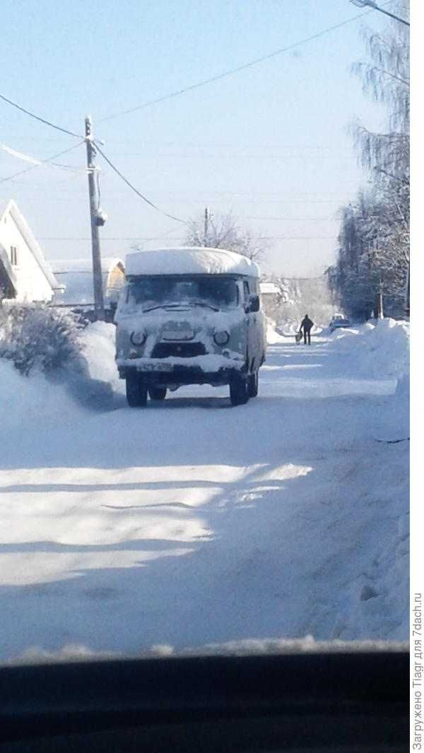 Едут по деревне заснеженные машины. Дорогу трактор уже почистил