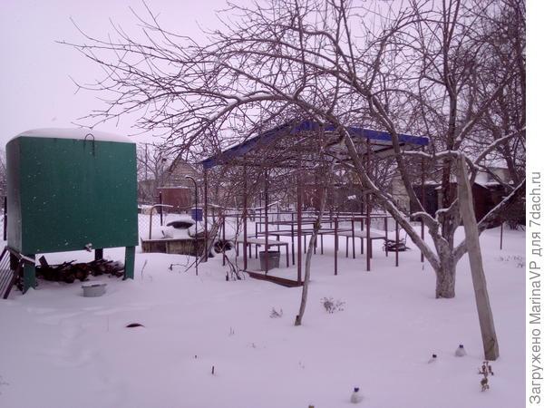 Заснеженная беседка. Розочки укрыты снегом.