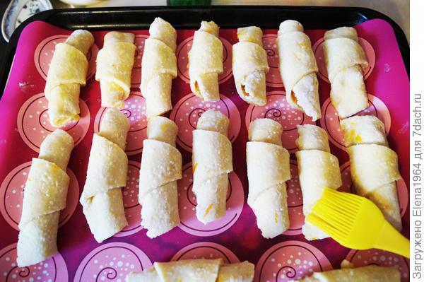 Рогалики выложить на противень, застеленный силиконовым ковриком. Смазать слегка растительным маслом или сладкой водичкой и поставить запекать  в духовку, разогретую до 180 гр. до зарумянивания