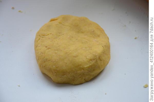 Яйцо разбить в отдельную миску, взболтать, часть яйца оставить для смазки теста.  Добавить к мучной крошке половину яйца и 1-2 ст. л. ледяной воды, быстро замесить тесто.