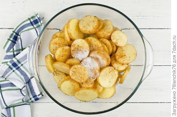 Картофель обваляйте в специях и масле