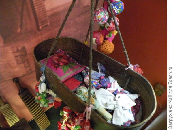 Деревянная люлька для младенца и его игрушки