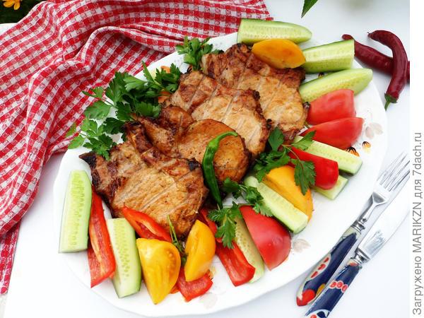 Готовые стейки из свинины с овощами и зеленью