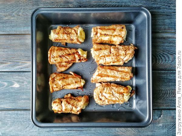 Форму смазываем растительным маслом и выкладываем фаршированные куриные рулетики.