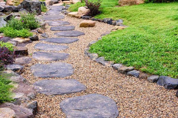 Комбинированный вариант: шаговые элементы из натурального камня, отсыпка галькой, каменный бордюр