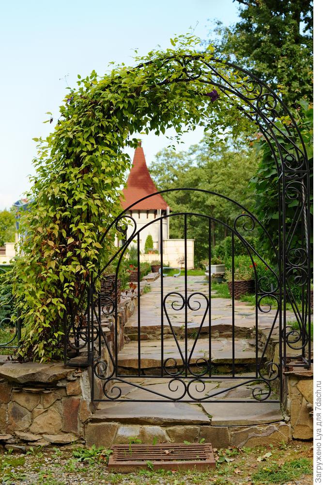 Интересное сочетание каменного цоколя, металлической ограды и ажурной невысокой арки с калиткой